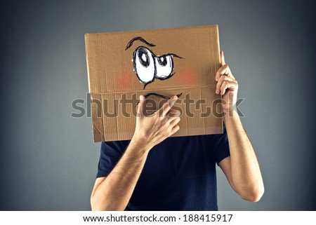 Man thinking with cardboard box on his head with serious emoticon face expression.