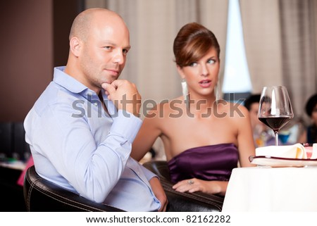 man thinking, woman suspicious at restaurant table - stock photo