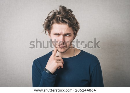 Man thinks finger to his mouth. Gray background - stock photo