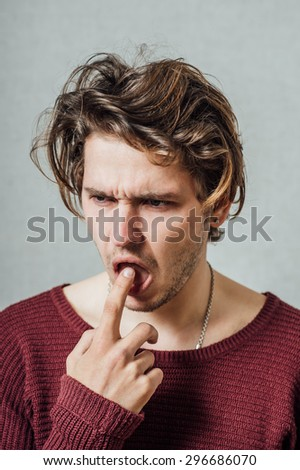 Man thinks with finger in his mouth. Gray background - stock photo