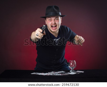Man threatened with a gun in anger, playing cards. - stock photo
