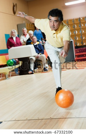 Man throwing bowling ball at bowling alley - stock photo