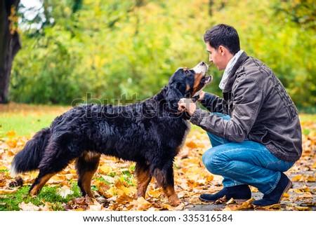Man throwing stick for his dog to retrieve - stock photo