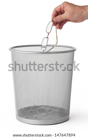 Man throws glasses in the dustbin, isolated on white. - stock photo