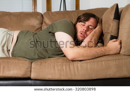 Man tired he falls asleep on the couch - stock photo