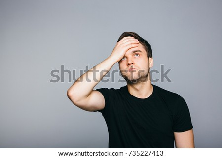 Man  tired  touching his head while standing against grey background.