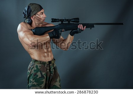 Man to aim in aim. He wants to shoot a sniper rifle. He had big muscles and naked torso. - stock photo