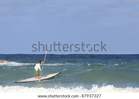 Man to paddle on a stand up paddle boat (Hasake) in the sea