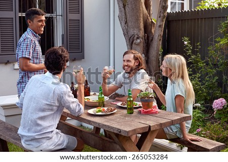 man toasting speech at friends outdoor garden party with wine drinks - stock photo