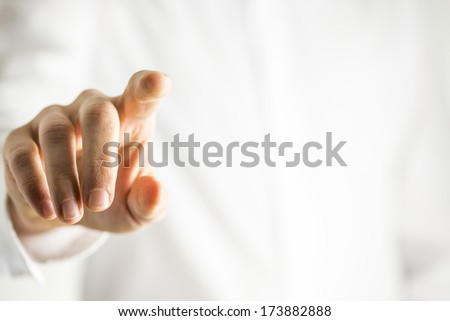 Man touching a blank virtual screen or computer interface with his finger to input data, identify himself, activate the screen or gain access - stock photo