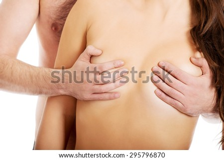 Man touching beautiful woman's breast.