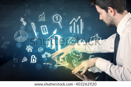 Man touching technology smart table with business icons and symbols - stock photo