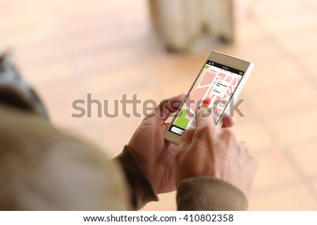 man touching the screen of his smartphone showing gps app. All screen graphics are made up. - stock photo