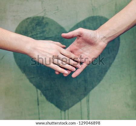 Man touching woman's hand with a heart painted wall in background - stock photo