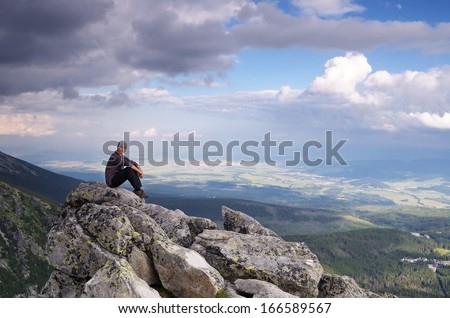 Man tourist is sitting on a rock in the mountains