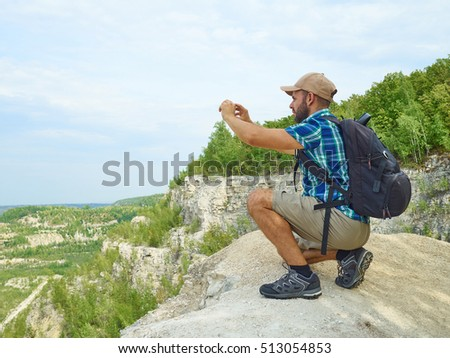 Man tourist is using a smartphone while sitting on the edge of a cliff in the mountains. Caucasian male outdoors in nature. Hiker young man with backpack .