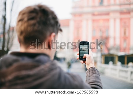Man / tourist taking photos of a monument with mobile phone - stock photo