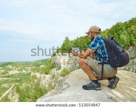 Man tourist uses tablet computer sitting on the edge of a cliff in the mountains. Caucasian male outdoors in nature. Hiker young man with backpack .