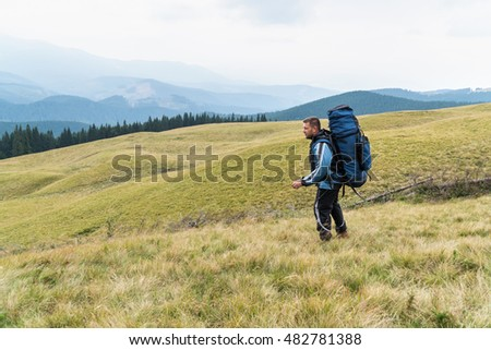Man tourist with a big backpack goes on the grass against mountains