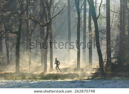 Man trail running in the forest on a foggy, spring morning. - stock photo