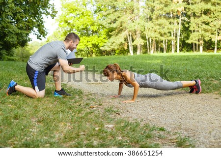 Man trainer motivates women to do push-ups - stock photo