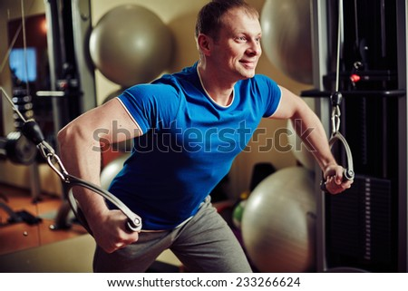 Man training lifting weights at exercise machine - stock photo