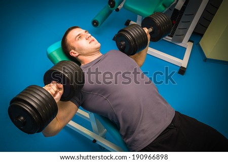 man training with dumbbells in the gym