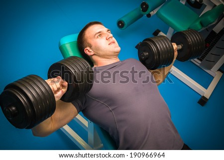 man training with dumbbells in the gym - stock photo