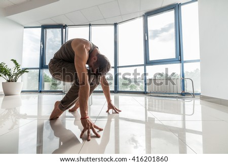 Man Training Yoga On The Floor At The Gym In Front Of A Window