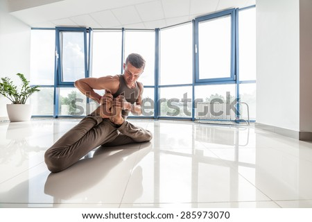 Man Training Yoga On The Reflection Floor At The Gym Across A Big Window