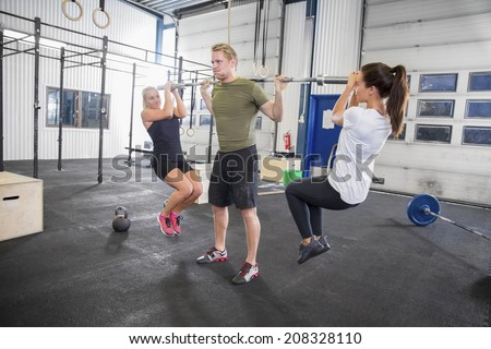 Man trains squats with girls as weights - stock photo