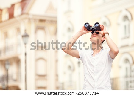 Man travel through the old city. Man with binoculars in hand. Young business man in the city, he looks binoculars. Urban modern man, summer day. See the goal, look forward with pleasure to travel. - stock photo