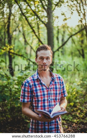 Man traveler is reading electronic book on portable touch pad, while is relaxing in the fresh air during trip in Asia.Male freelancer is working on digital tablet, while is sitting against jungle view
