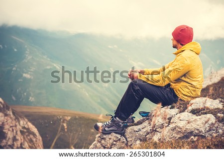 Man Traveler relaxing alone in Mountains Travel Lifestyle concept cloudy nature landscape on background  - stock photo