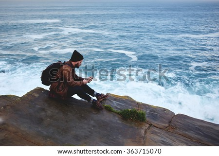 Man traveler watching world map via app on mobile phone while relaxing near ocean during his autumn trip, young male reading text message on cell telephone while sitting on a rock near sea with waves