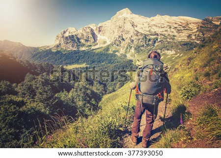 Man Traveler with backpack mountaineering Travel Lifestyle concept mountains on background Summer vacations activity outdoor  - stock photo