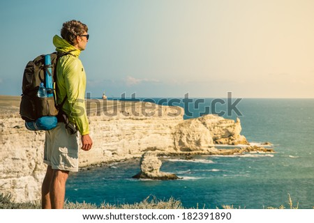 Man Traveler with backpack relaxing outdoor Sea and Rocks coastal on background Freedom Lifestyle concept - stock photo