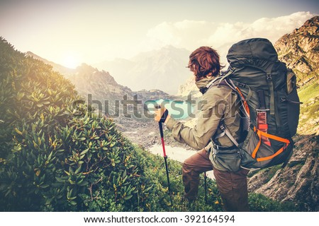 Man Traveler with big backpack mountaineering Travel Lifestyle concept lake and mountains on background Summer extreme vacations outdoor  - stock photo