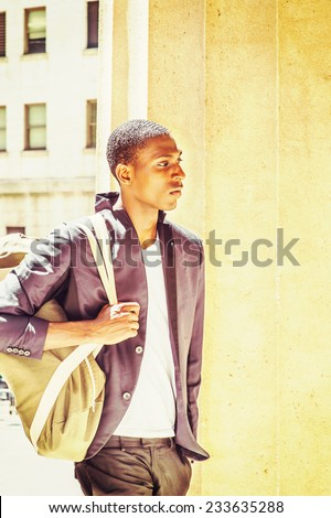 Man Traveling. Carrying a shoulder bag, a young black college student is walking though columns on campus, sad, thinking, lost in thought.  - stock photo