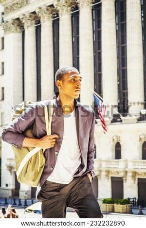 Man Traveling. Carrying a shoulder bag, walking up, a young black college student is standing in the front of an office building, confidently looking forward.  - stock photo