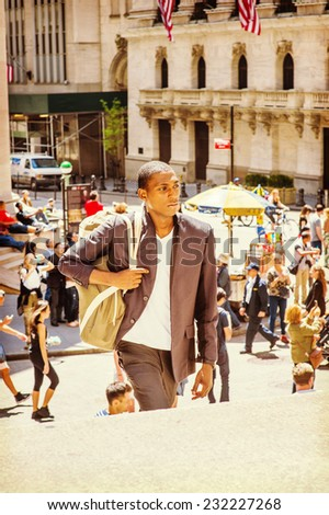 Man Traveling. Carrying a shoulder bag, walking up on steps, a young black college student is traveling on street in a big city. Many people on background. - stock photo