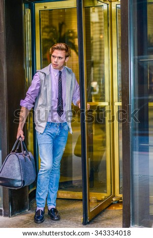 Man Traveling in New York. American professional, wearing sleeveless hoodie, pink shirt, necktie, jeans, leather shoes, carrying hand bag, walking out from store revolving door, looking forward.