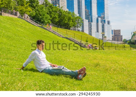 Man traveling, working in New York. Wearing white shirt, jeans, sneakers, a young college student sitting on green lawn with stairs to business district, reading, working on a laptop computer. - stock photo
