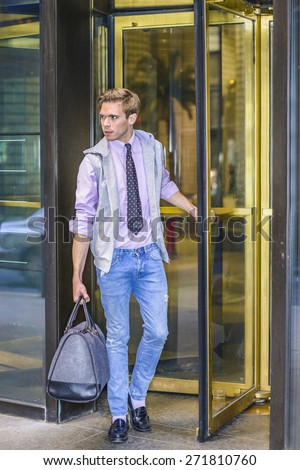 Man Traveling. Young blonde professional, wearing sleeveless hoodie, long sleeve, pink shirt, necktie, jeans, leather shoes, carrying a hand bag, walking out from store revolving door, looking forward - stock photo