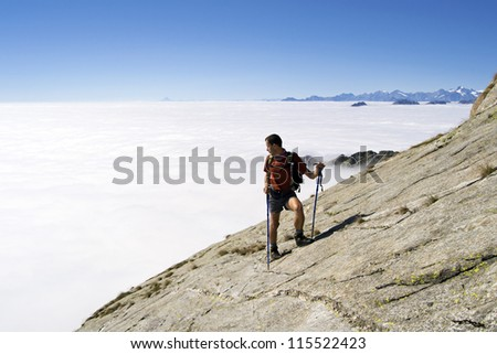 Man trekking in the Alps over the clouds in a beautiful sunny day. Gran Paradiso National Park, Italy