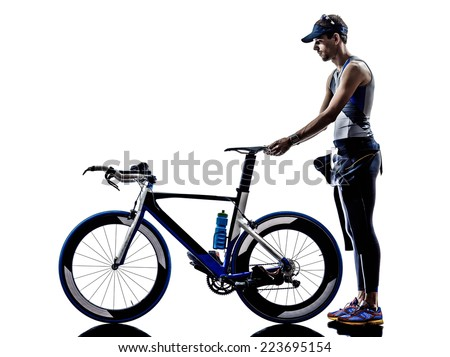 man triathlon iron man athlete standing with all his equipment in silhouette on white background - stock photo