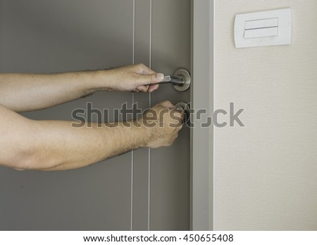 man try to open the locked door by the key - can use to display or montage on products