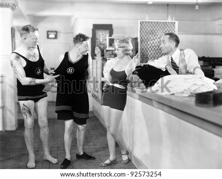 Man trying on an oversized shirt in a store with his friends - stock photo