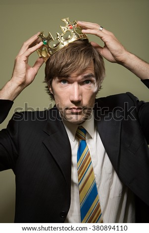 Man trying on crown - stock photo
