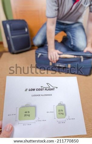 Man trying to close full hand luggage for comply low cost airlines restrictions - stock photo